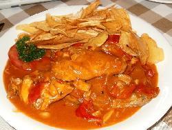 Pollo en porciones cocido con tomate y panceta